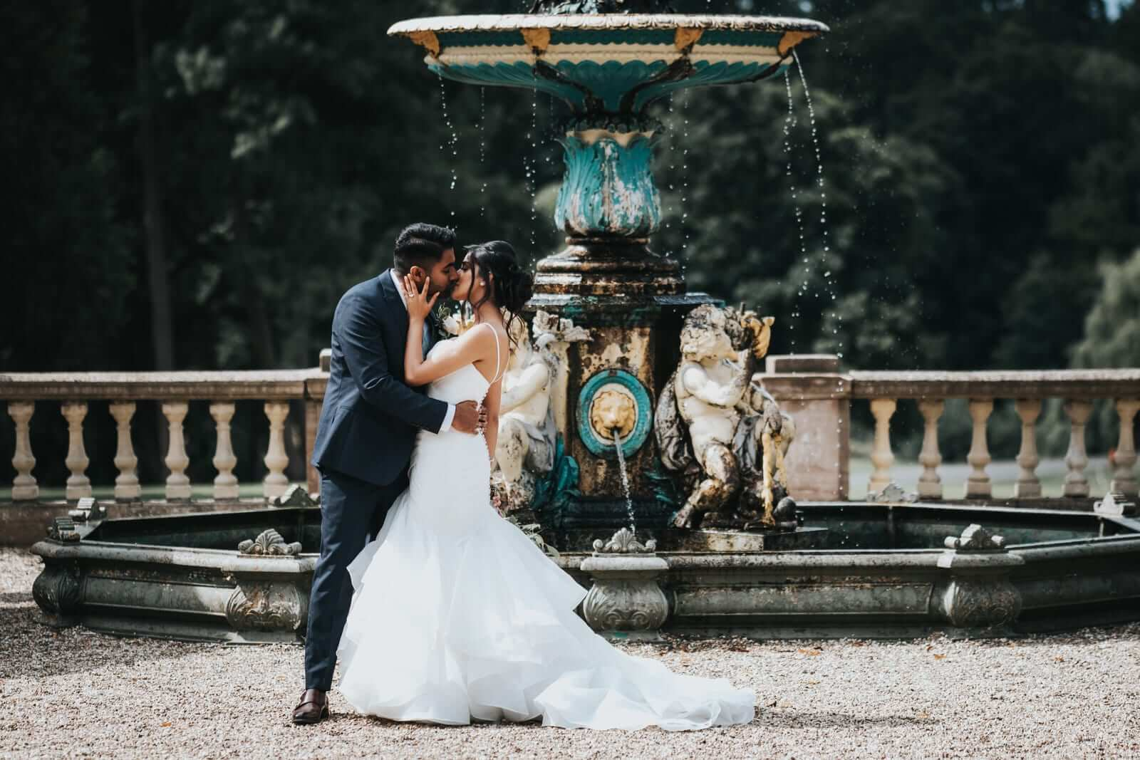 Brides and groom kissing in the park.